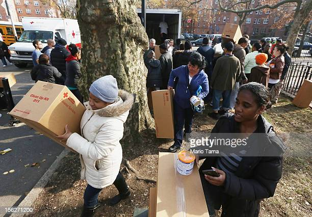 People carry boxes of goods donated by the Red Cross in the Red Hook neighborhood on November 12 2012 in the Brooklyn borough of New York City The...