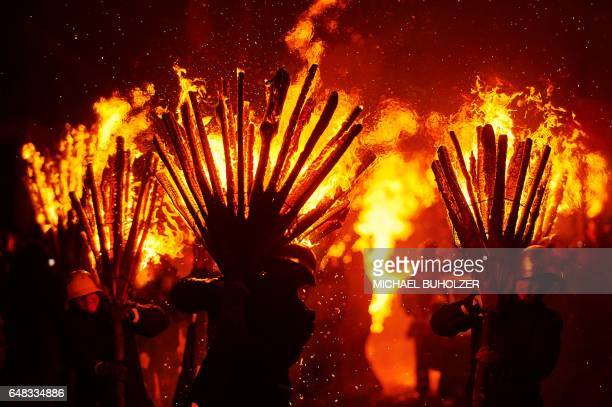 TOPSHOT People carry burning bundles of pinewood chips on their shoulders during the 'Chienbase' procession on March 5 2017 in Liestal northern...