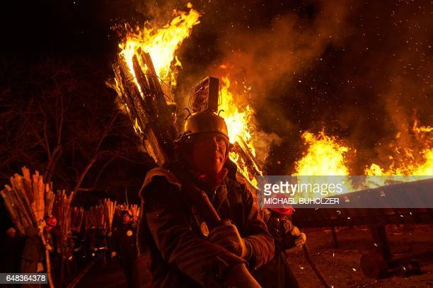 People carry burning bundles of pinewood chips on their shoulders during the 'Chienbase' procession on March 5 2017 in Liestal northern Switzerland...