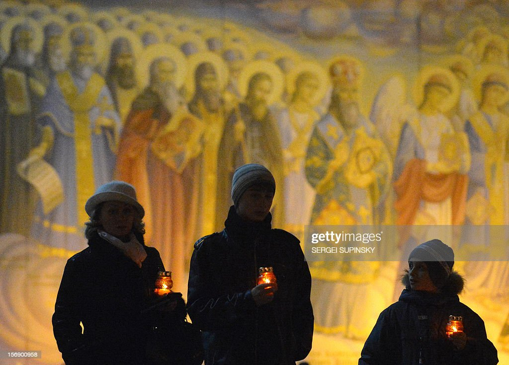 People carry candles in front of frescos in memory of the victims of the Holodomor famine in Kiev on November 24, 2012. Ukraine marked 80 years since the Stalin-era Holodomor famine, one of the darkest pages in its entire history that left millions dead and which is regarded by many as a genocide. The 1932-33 famine took place as harvests dwindled and Josef Stalin's Soviet police enforced the brutal policy of collectivising agriculture by requisitioning grain and other foodstuffs. AFP PHOTO/ SERGEI SUPINSKY