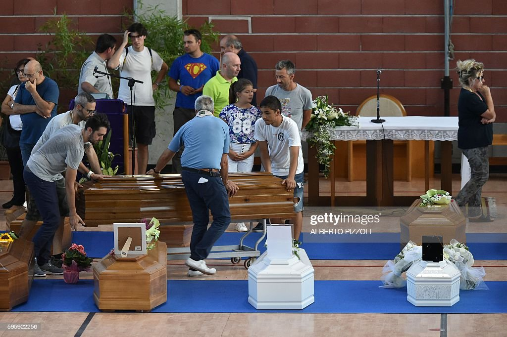 People carry coffins of earthquake victims in a gymnasium arranged in a chapel of rest on August 26 in Ascoli Piceno two day after a 62magnitude...