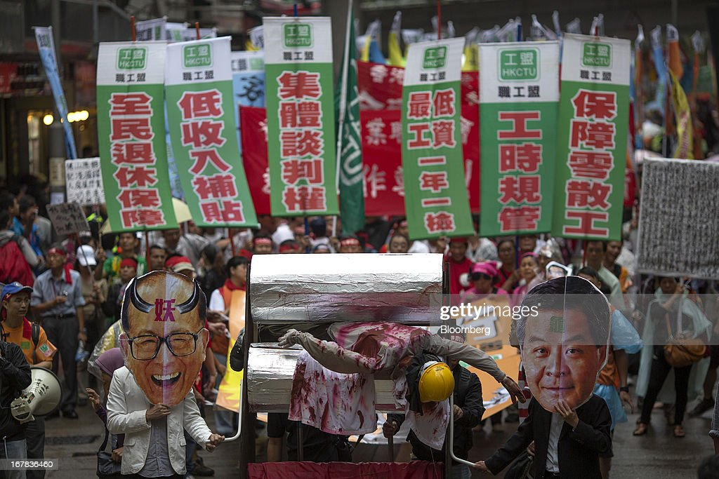 People carry effigies of billionaire Li Ka-shing, chairman of Hutchison Whampoa Ltd. and Cheung Kong (Holdings) Ltd., left, and Leung Chun-ying, Hong Kong's chief executive, right, during a Labor Day march in Hong Kong, China, on Wednesday, May 1, 2013. Thousands of Hong Kong residents took to the streets today for Labor Day marches to petition for better labor conditions and in support of strike action by workers at docks operated by Li. Photographer: Jerome Favre/Bloomberg via Getty Images