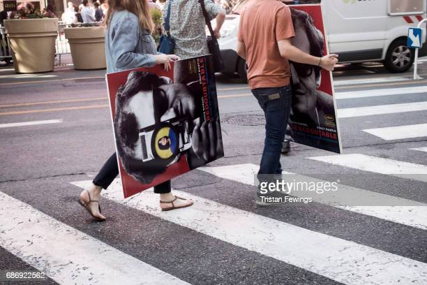People carry film posters during the 70th annual Cannes Film Festival at on May 22 2017 in Cannes France