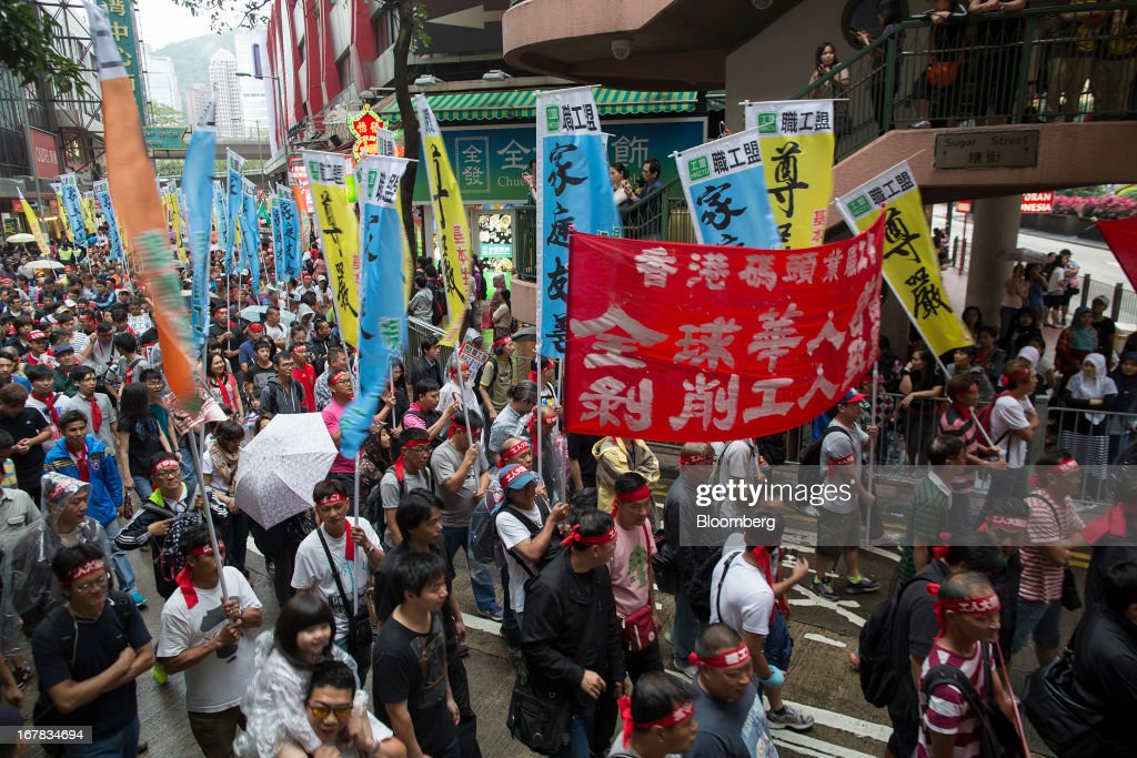 People carry flags and chant slogans during a Labor Day march in Hong Kong, China, on Wednesday, May 1, 2013. Thousands of Hong Kong residents took to the streets today for Labor Day marches to petition for better labor conditions and in support of strike action by workers at docks operated by billionaire Li Ka-shing. Photographer: Jerome Favre/Bloomberg via Getty Images