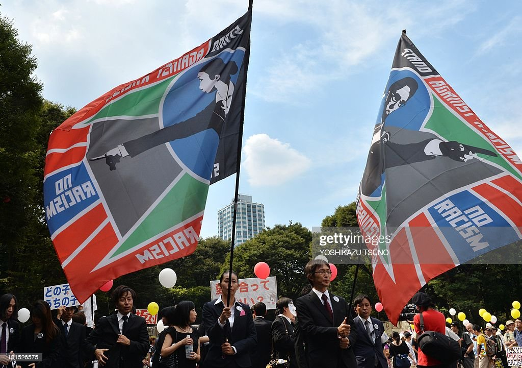 People carry flags during a march against racism in Tokyo on September 22, 2013. Some 2,000 people took part in an anti-discrimination rally to commemorate the 50th anniversary of the March on Washington and Martin Luther King Jr.'s 'I have a dream' speech on August 28, 1963. AFP PHOTO / Yoshikazu TSUNO