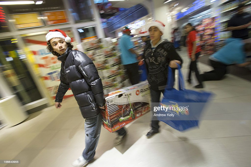 People carry items at the Black Thursday sale at the Toys 'R' Us store in Times Square November 22, 2012 in New York City.The store got a head start on the traditional Black Friday sales by opening their doors at 8pm on Thanksgiving night.