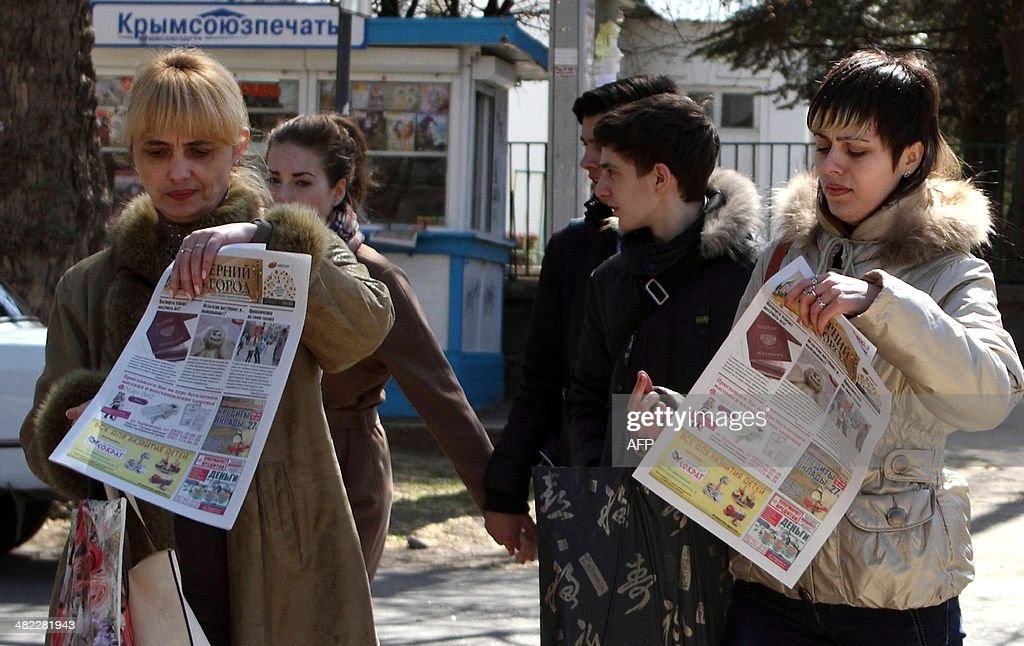 People carry local newspapers with photos of a Russian passport on their front pages in the Crimean capital Simferopol on April 3, 2014. Crimeans have been given a month to expressly state that they want to stay Ukrainian -- or they will automatically become Russian citizens, although they still have to obtain passports.