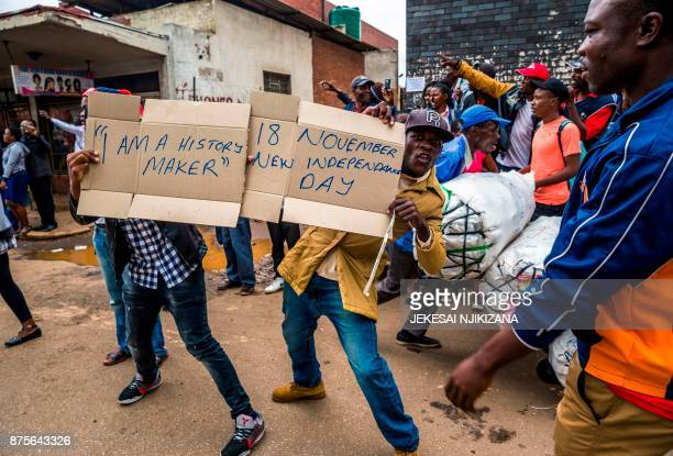 TOPSHOT People carry makeshift signs during a demonstration demanding the resignation of Zimbabwe's president on November 18 2017 in Harare Zimbabwe...