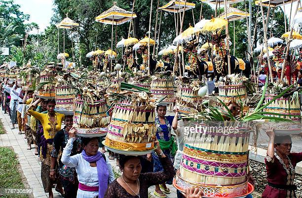 People carry offerings to the cremation site during a Balinese Hindu mass cremation on August 18 2013 in Ubud Bali Indonesia More than 60 corpses...