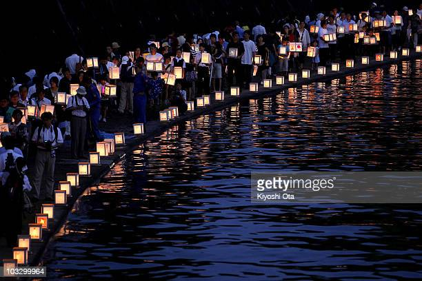 People carry paper lanterns to release onto the Urakami River for peace and the atomic bomb victims as they walk along the river on August 9 2010 in...