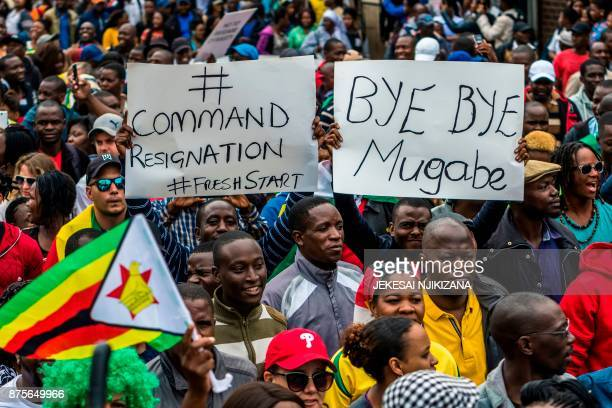 TOPSHOT People carry placards during a demonstration demanding the resignation of Zimbabwe's president on November 18 2017 in Harare Zimbabwe was set...