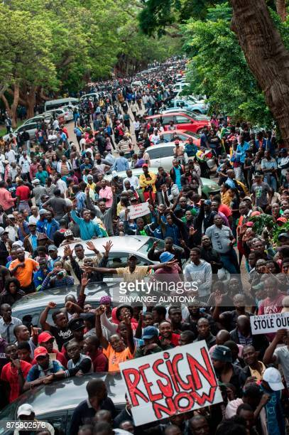People carry placards reading 'resign now' during a demonstration demanding the resignation of Zimbabwe's president outside the State House the...