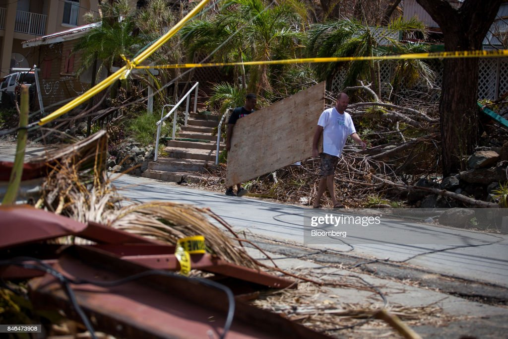 People carry plywood in front a damaged building after Hurricane Irma in St John, U.S. Virgin Islands, on Tuesday, Sept. 12, 2017. After being struck by Irma last week, the U.S. Virgin Islands couldnt look less like a tourist destination. Many local residents are giving up and getting out after losing everything to the category 5 storm,even as the local authorities in the U.S. territory say they are determined to rebuild the islands. Photographer: Michael Nagle/Bloomberg via Getty Images