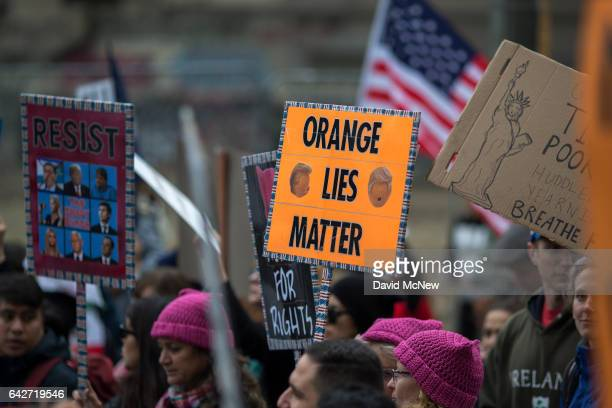People carry signs during the Immigrants Make America Great March to protest actions being taken by the Trump administration on February 18 2017 in...