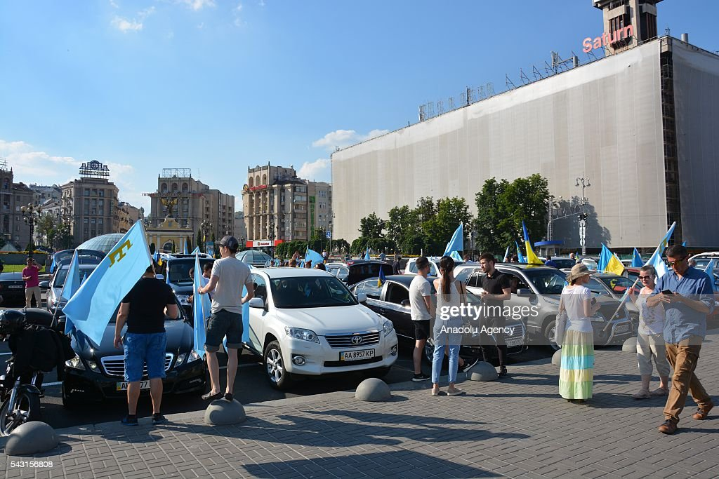 People carry the 40 metre-long Crimean Tatar flag during the 'Crimean Tatar Flag Day' in Kiev, Ukraine on June 26, 2016.