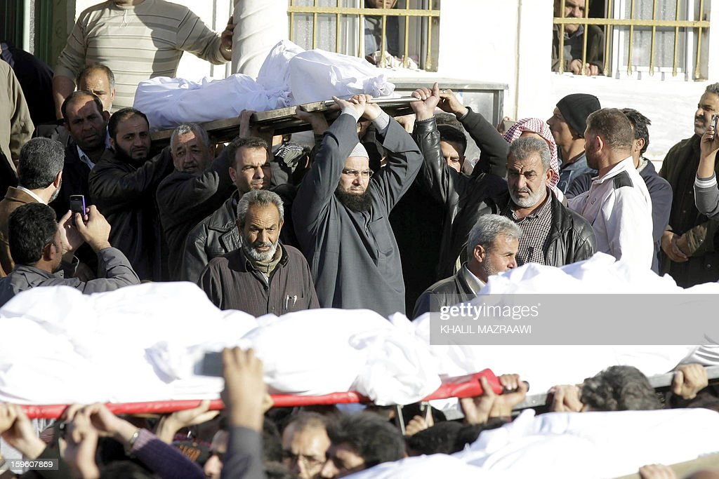 People carry the bodies of Syrian refugees who were killed the day before during an explosion during their funeral in the northern city of Ramtha, which houses hundreds of refugees, on January 17, 2013. Eight Syrian refugees were killed when a kerosene heater exploded and the caravan in which they were living caught fire, and another four were hurt in the incident.