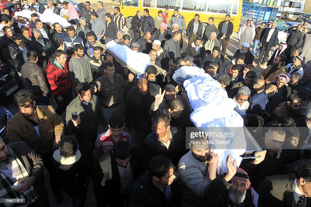People carry the bodies of Syrian refugees who were killed the day before during an explosion during their funeral in the northern city of Ramtha, which houses hundreds of refugees, on January 17, 2013. Eight Syrian refugees were killed when a kerosene heater exploded and the caravan in which they were living caught fire, and another four were hurt in the incident. AFP PHOTO KHALIL MAZRAAWI