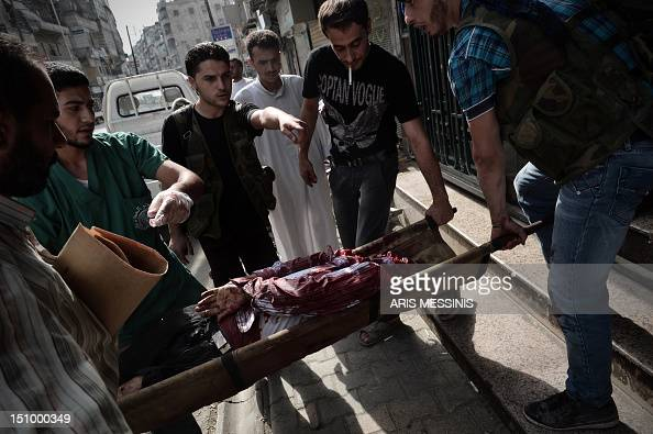 People carry the body of a civilian who was wounded during shelling by Syrian government forces outside a hospital in Syria's northern city of Aleppo...