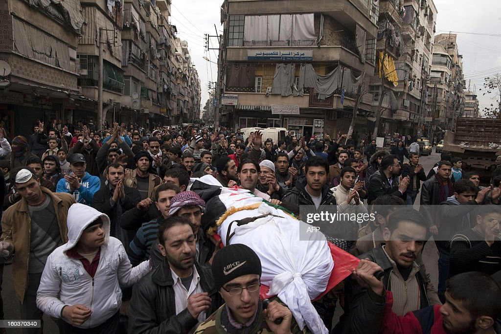 People carry the body of a deceased man during a funeral procession in the Bustan al-Qasr district of Aleppo, on January 30, 2013. Syria's opposition charged that 'global inaction' was giving Bashar al-Assad's regime a license to kill, a day after dozens of young men were found shot execution-style in the city of Aleppo. AFP PHOTO/JM LOPEZ