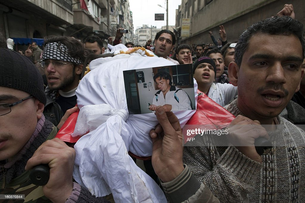 People carry the body of a deceased man during a funeral procession in the Bustan al-Qasr district of Aleppo, on January 30, 2013. Syria's opposition charged that 'global inaction' was giving Bashar al-Assad's regime a license to kill, a day after dozens of young men were found shot execution-style in the city of Aleppo.