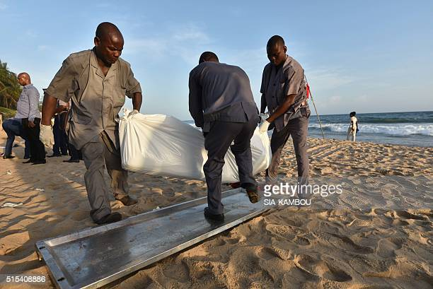 People carry the body of a victim following after gunmen went on a shooting rampage in the Ivory Coast resort of GrandBassam on March 13 2016...