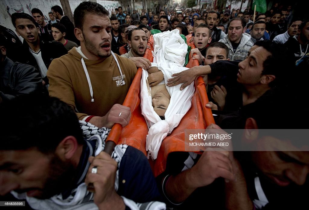 People carry the body of Bilal Samir Oweida, a 20-year-old Palestinian, during a funeral procession in Beit Lahia, northern Gaza Strip on January 24, 2014. Bilal Samir Oweida was 'shot in the chest by Israeli soldiers' east of Jabaliya said Ashraf al-Qudra, a spokesman for the Hamas-run health ministry as Israeli forces said he had entered 'a prohibited area'.