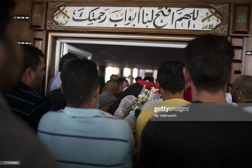 People carry the body to the mosque during the funeral held for three Palestinians killed during IDF operation at Kalandia refugee camp on August 26, 2013 in Ramallah, West Bank. At least 15 people were injured as Palestinians clash with undercover Israeli troops.