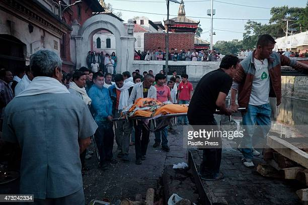 People carry the body to the Pasphutinah Temple in Kathmandu for a massive cremation A strong earthquake of magnitude 74 rocked Nepal capital...