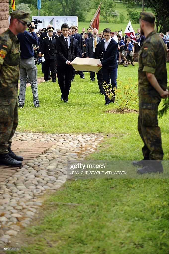 People carry the coffin of Hans Winckelmann, a German soldier who died in WWI, during his burial at the German WWI cemetery of Romagne-sous-Montfaucon, eastern France on May 28, 2016, as part of the Verdun battle commemoration. / AFP / JEAN