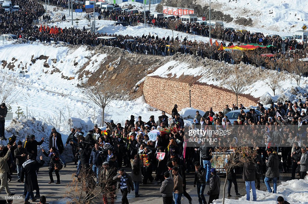 People carry the coffin of late Kurdish activist Sakine Cansiz, shot dead in the French capital, during the funeral on January 18, 2013 in Tunceli, her hometown in the Kurdish majority southeast of Turkey. People gathered inTunceli, to pay a final tribute to Sakine Cansiz who was assassinated in Paris last week. The growing crowd of participants, men and women adorned in white scarves, a symbol of peace, marched in a funeral many in Turkey feared would turn into a violent protest. The three women, one of them Sakine Cansiz, a co-founder of the outlawed Kurdistan Workers' Party (PKK), were found fatally shot, at least three times in their heads, at a Kurdish centre in Paris last week. French police were hunting the unknown assailants. AFP PHOTO/BULENT KILIC