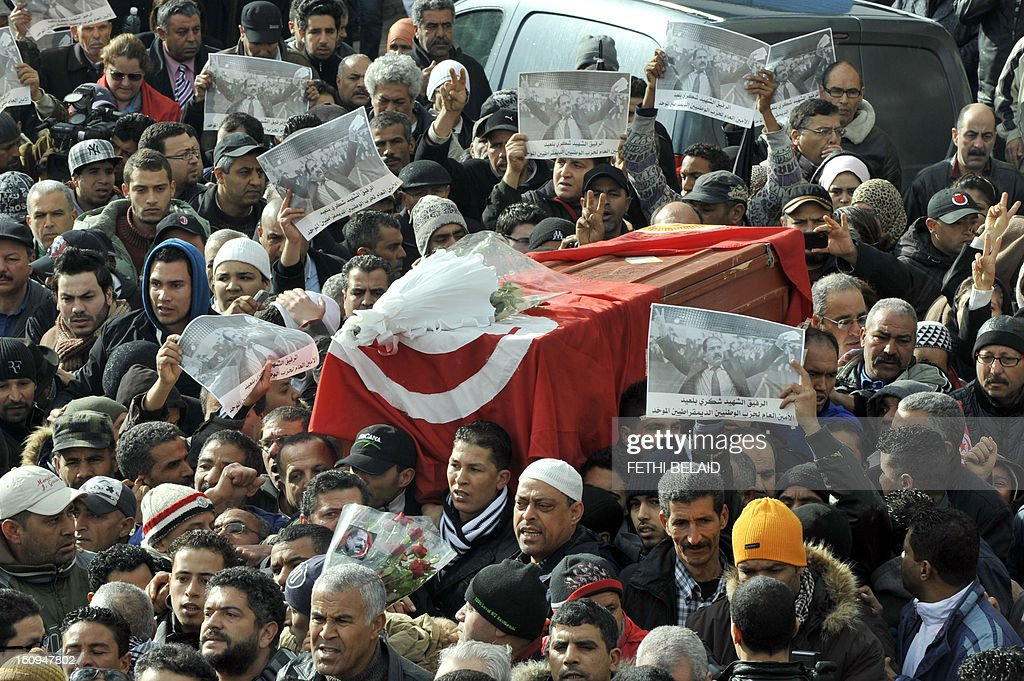 People carry the coffin of late opposition leader Chokri Belaid during his funeral procession which makes its way to the nearby cemetery of El-Jellaz where Belaid is to be buried on February 8, 2013 in the Djebel Jelloud district, a suburb of Tunis. Thousands of people attend the funeral while Tunis is at a near standstill, with streets deserted, shops shut and public transport at a minimum as a general strike called by a powerful trade union after Bellaid was murdered took effect.