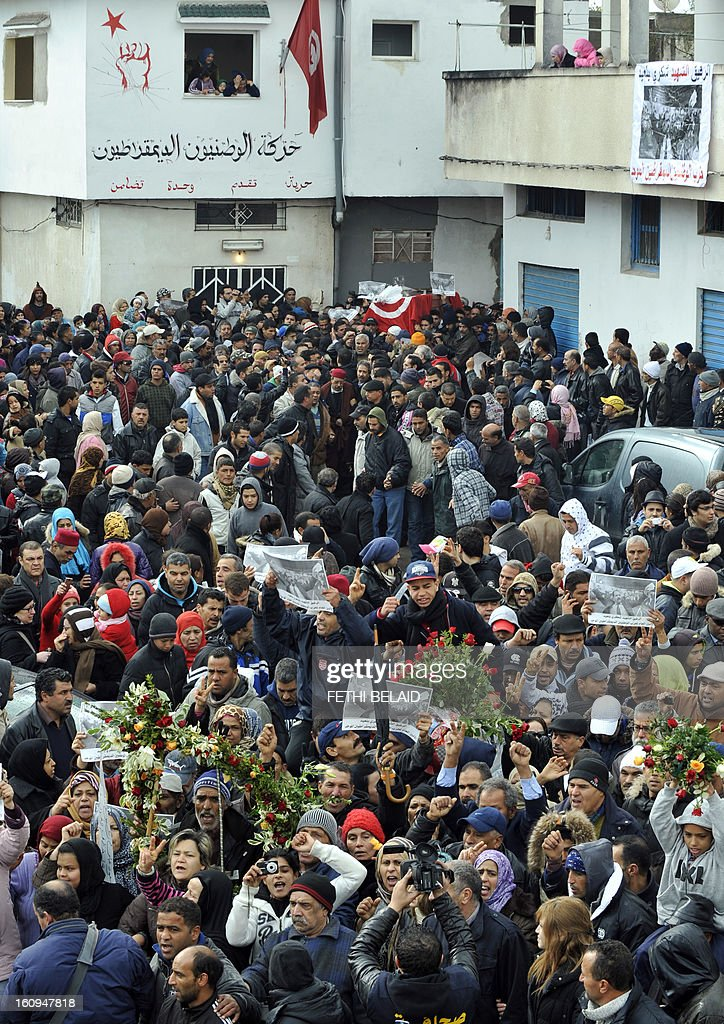 People carry the coffin of late opposition leader Chokri Belaid (background) during his funeral procession which makes its way to the nearby cemetery of El-Jellaz where Belaid is to be buried on February 8, 2013 in the Djebel Jelloud district, a suburb of Tunis. Thousands of people attend the funeral while Tunis is at a near standstill, with streets deserted, shops shut and public transport at a minimum as a general strike called by a powerful trade union after Bellaid was murdered took effect.