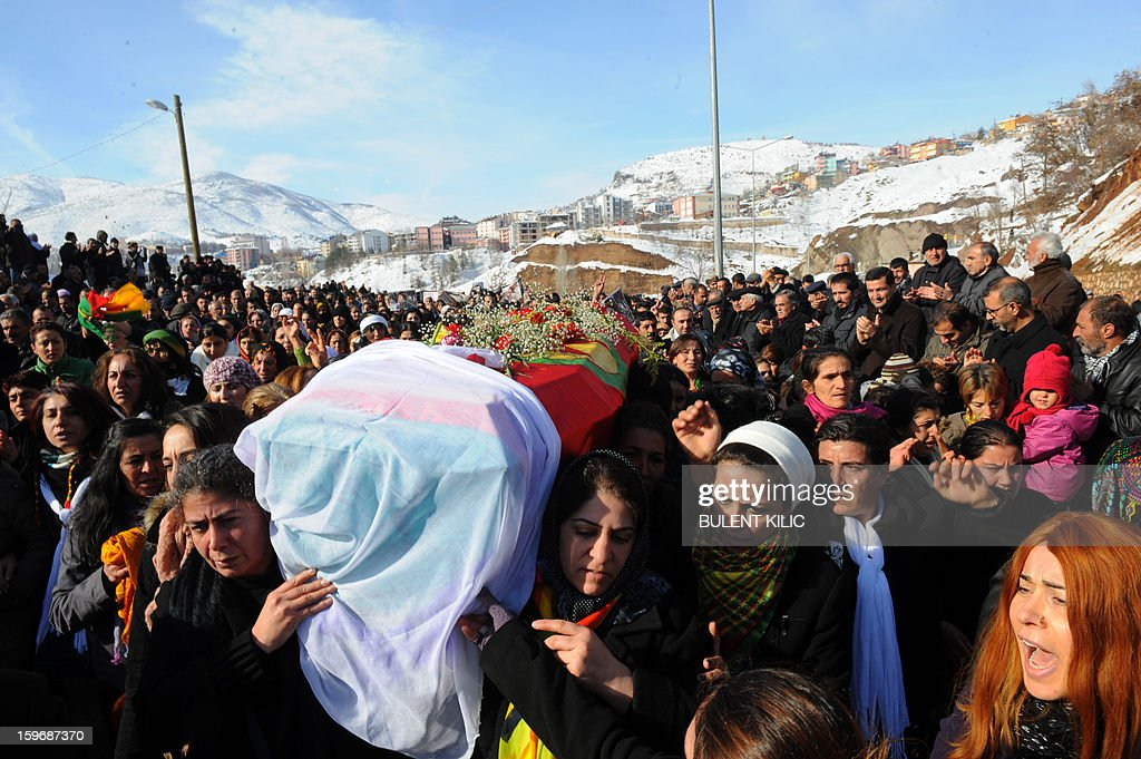 People carry the coffin of the Kurdish activist Sakine Cansiz, shot dead in the French capital, on January 18 in Tunceli. People gathered on January 18 in Tunceli, to pay a final tribute to Sakine Cansiz who was assassinated in Paris last week. The growing crowd of participants, men and women adorned in white scarves, a symbol of peace, marched in a funeral many in Turkey feared would turn into a violent protest. The three women, one of them Sakine Cansiz, a co-founder of the outlawed Kurdistan Workers' Party (PKK), were found fatally shot, at least three times in their heads, at a Kurdish centre in Paris last week. French police were hunting the unknown assailants. AFP PHOTO/BULENT KILIC