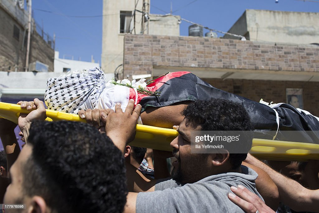People carry the corpse during the funeral prossesion held for three Palestinians killed during IDF operation at Kalandia refugee camp on August 26, 2013 in Ramallah, West Bank. At least 15 people were injured as Palestinians clash with undercover Israeli troops.