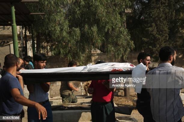 People carry the dead bodies of regime attack victims after Assad Regime's forces carried out their strikes over the deconflict zone Kafr Batna...