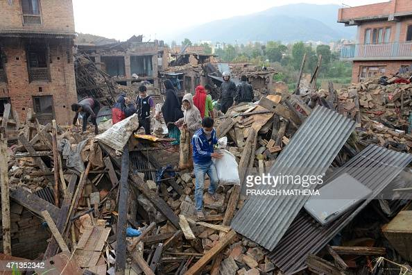 People carry their belongings amidst the rubble of collapsed houses in Bhaktapur on the outskirts of Kathmandu on April 27 two days after a 78...