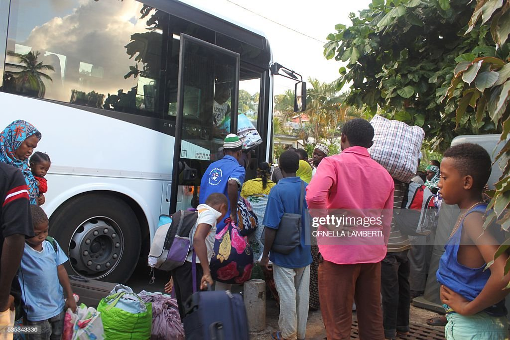 People carry their belongings as they get into a bus on May 29, 2016 in Ouangani, center part of the French overseas region and department Mayotte, to go to the capital, Mamoutzou. Around 500 'illegal immigants', mostly from Comoros, evicted from their house by local Mayotte inhabitants, camp out since May 15, 2016 on Republique square at Mamoudzou as associations try to rehouse them. Rising anti-migrant anger has seen groups of up to 100 men gather in villages with lists of houses belonging to foreigners and going from door to door forcing them to leave. Police have tried to prevent violence, but have been unable to stop the pressure mounting on foreigners -- including many who are living on Mayotte legally -- who have fled their homes in fear. Mayotte opted to remain under French rule when the other islands in the Comoros archipelago chose independence in 1975. / AFP / ORNELLA