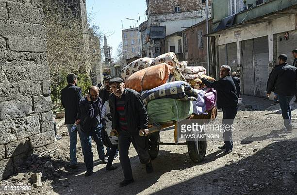 People carry their belongings on a barrow as they return back to their home after clashes ended in the Sur district of Diyarbakir on March 13 2016...