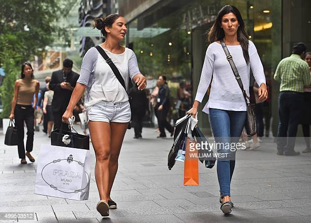 People carry their shopping bags through Sydney's Pitt Street Mall on December 2 as Australia's economy grew 09 percent in the third quarter for an...