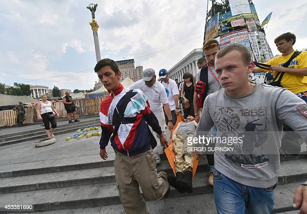 People carry wounded after clashes of residents of Kiev with Maidan selfdefence activists on August 9 2014 K as thousands of the residents came to...