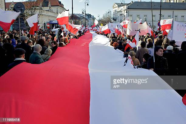 People carrying a giant Polish flag gather in front of the Presidential Palace during a memorial service commemorating the Smolensk plane crash...