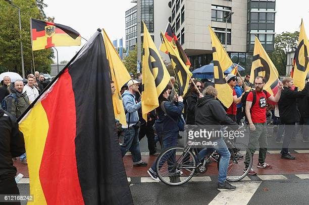 People carrying flags showing the symbol of the rightwing panEuropean Identitarian movement march with supporters of the Pegida movement on German...