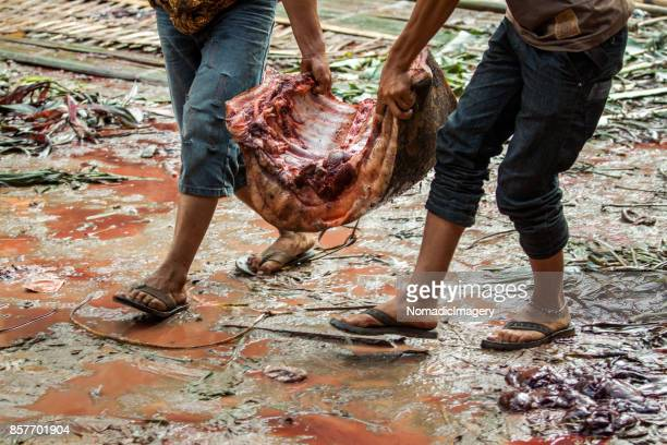 People carrying huge slabs of raw meat at animal sacrifice ritual
