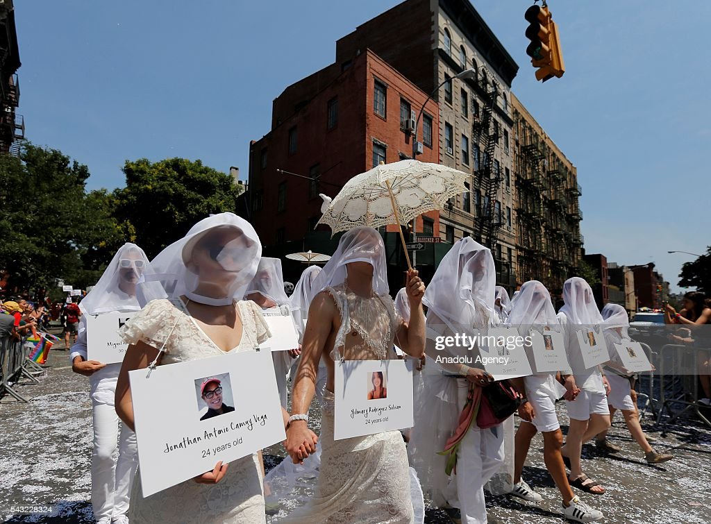 People carrying images of those killed in the nightclub shooting walk as part of a vigil during the 46th annual Gay Pride march June 26, 2016 in New York