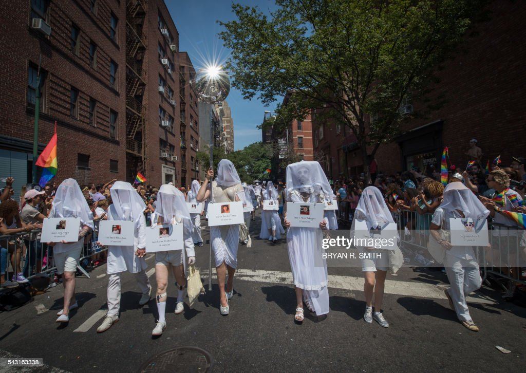 People carrying images of those killed in the Pulse nightclub shooting walk as part of a vigil during the 46th annual Gay Pride march June 26, 2016 in New York. New York kicked off June 26 what organizers hope will be the city's largest ever Gay Pride march, honoring the 49 people killed in the Orlando nightclub massacre and celebrate tolerance. / AFP / the 46th / Bryan R. Smith