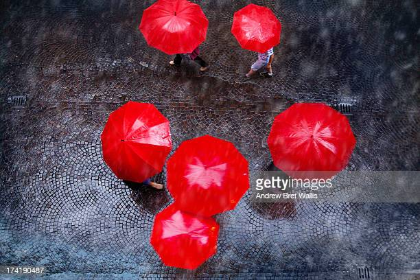 People carrying red umbrellas in the rain