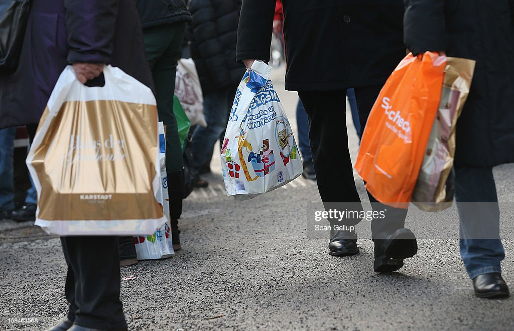 People carrying shopping bags wait for a bus on a shopping street in Steglitz district on December 17, 2012 in Berlin, Germany. Retailers are hoping for a strong Christmas season in Germany, one of the few countries whose economy has so far weathered the current Eurozone debt crisis relatively well.