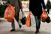 People carrying shopping bags walk past stores announcing Christmas specials in Berlin Mall on December 13 2014 in Berlin Germany Retailers across...