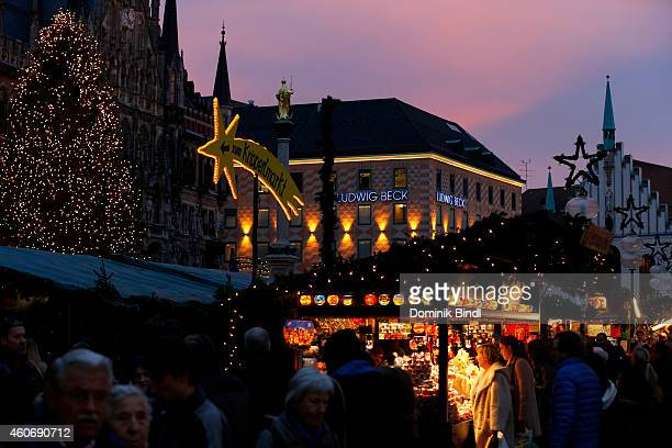 People carrying shopping bags walk past stores announcing Christmas specials and Christmas market stalls on Marienplatz on December 19 2014 in Munich...