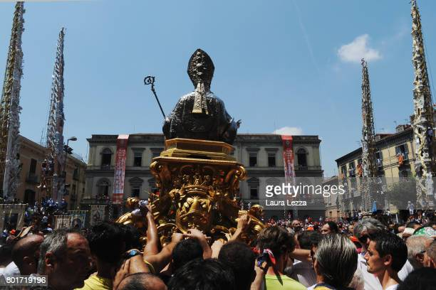 People carrying the statue of San Paolino after men carry a 25metre tall wood and papiermache statue called 'giglio' during the annual Festa dei...